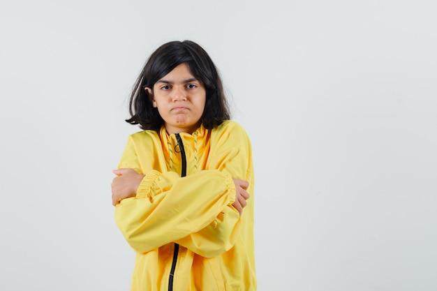 Молодая девушка в желтом бомбардировке дрожит от холода и выглядит серьезной