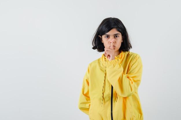 Молодая девушка в желтой куртке-бомбардировщике показывает жест молчания и выглядит серьезной