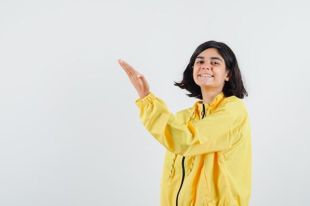 Молодая девушка в желтой бомбардировке протягивает руку влево и выглядит счастливой