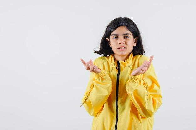 Молодая девушка в желтой куртке-бомбардировщике протягивает руки к камере и выглядит серьезно