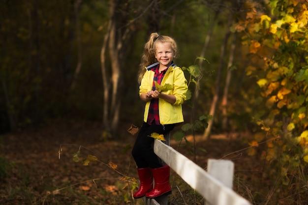Молодая девушка в желтой куртке и красные резиновые сапоги, сидя на деревянный забор в осеннем лесу. копировать пространство