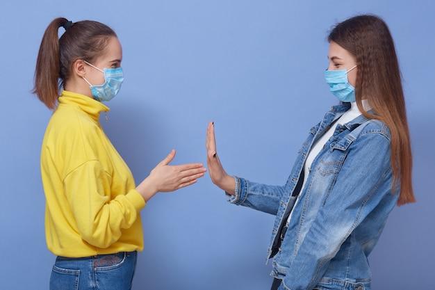 黄色いセーターを着た少女が握手をしている友人に挨拶したい