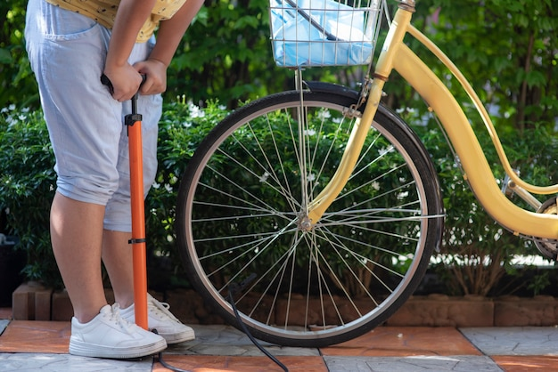 Young girl inflates the bicycle tire