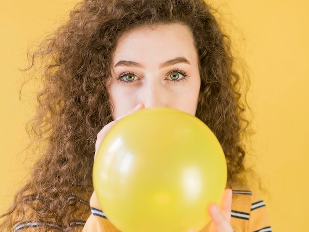 Young girl inflates a yellow balloon