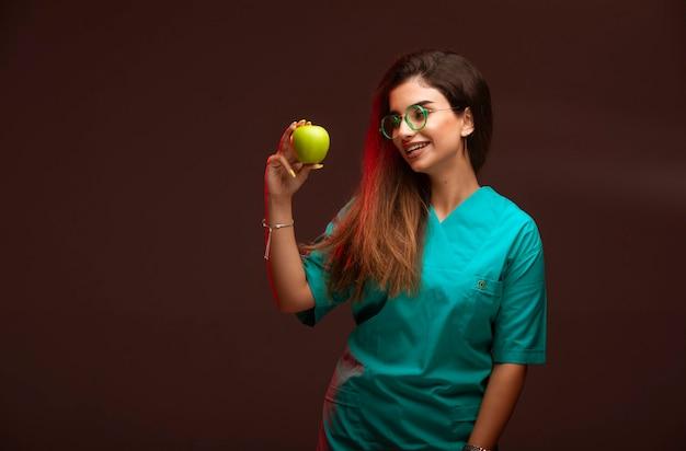 Молодая девушка представляет зеленое яблоко.