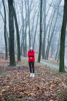 The young girl is alone lost in the foggy forest and feels fear, depression and loneliness