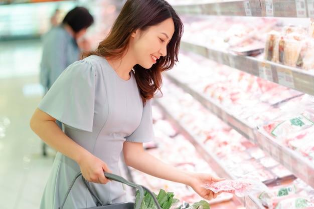 Молодая девушка покупает замороженные продукты в супермаркете