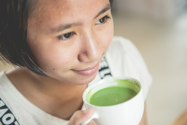 Young girl is drinking green tea in a coffee shop.