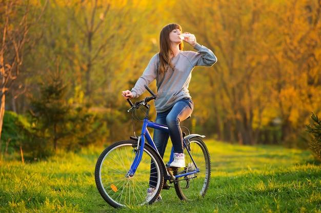 若い女の子は自転車で水を飲む
