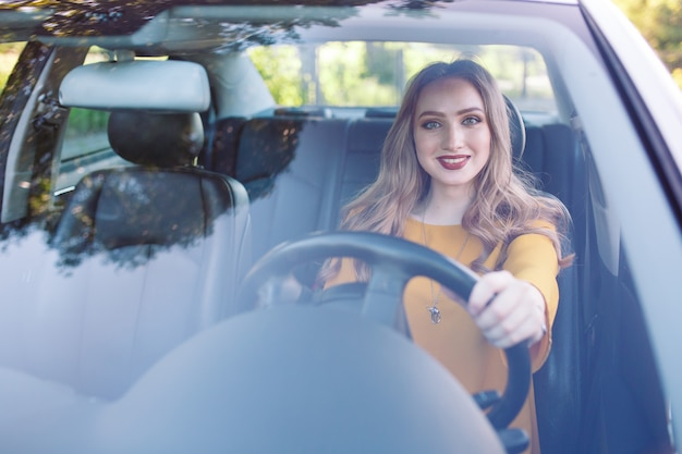 A young girl is driving a car.