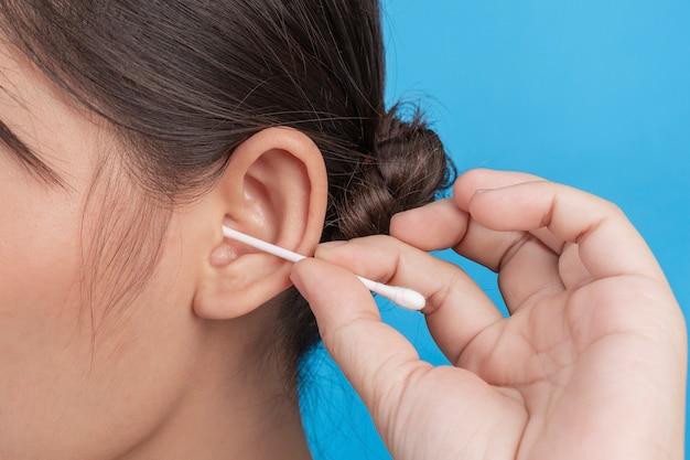 La ragazza sta raccogliendo l'orecchio con il tampone di cotone sulla parete blu, studio.
