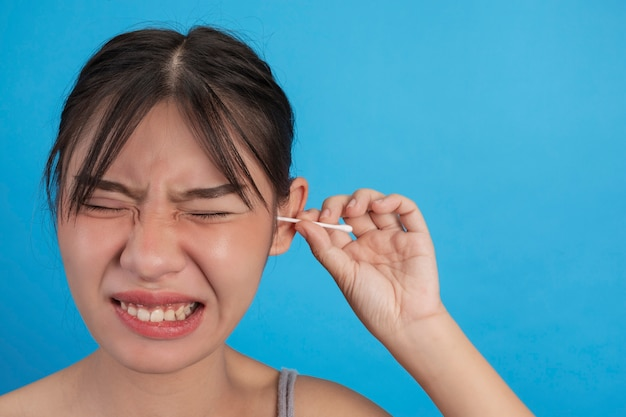 Young girl is ear picking with cotton swab on blue wall, studio.