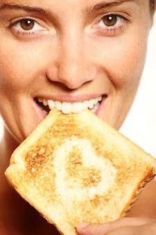 若い女の子は、ハートの形をした新鮮なトーストを食べています