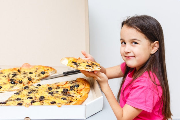 A young girl is eating a piece of pizza
