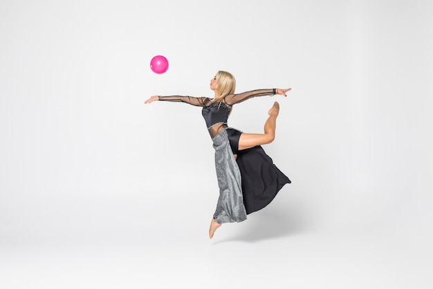 Young girl is engaged in art gymnastics with ball isolated