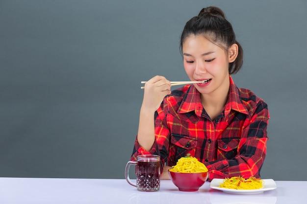 Молодая девушка любит есть спагетти дома