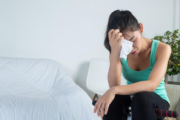Молодая девушка чувствует себя усталым и отдыхает после законченных упражнений в домашних условиях.