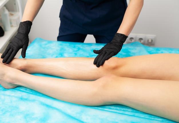 Молодая девушка получает лазерную эпиляцию для ног в салоне красоты