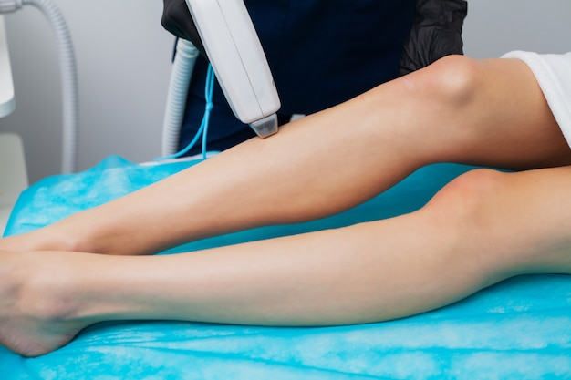 Young girl is getting laser hair removal for legs at beauty salon