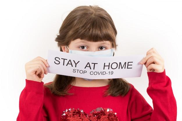 若い女の子がコロナウイルスの蔓延に対抗するために「家にいる」というマッサージのポスターを掲げている