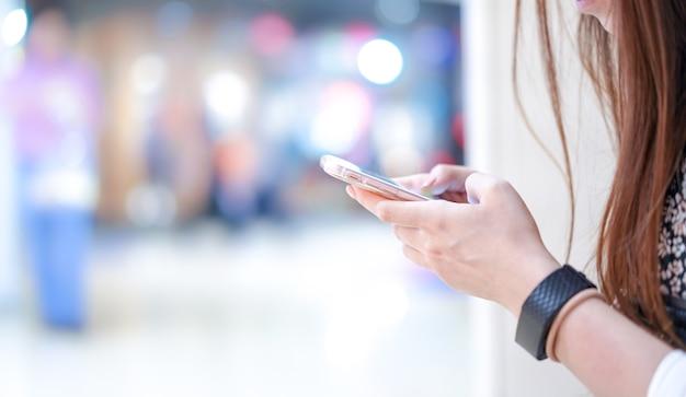 Молодая девушка держит в руке смартфон (около угла / обзора); играть, печатать, болтать, писать по электронной почте с размытым боке позади универмага.