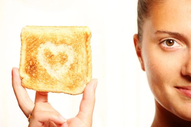 若い女の子は、ハートの形をしたトーストしたパンを持っています