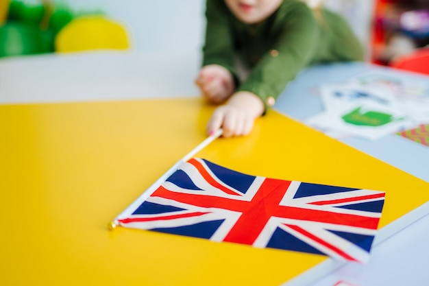 Young girl is holding union jack flag. british flag on the front view.