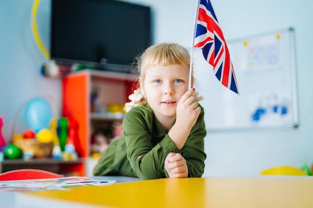 어린 소녀는 유니온 잭 깃발을 들고있다. 전면보기에 영국 국기입니다. 배경을 흐리게. 확대.