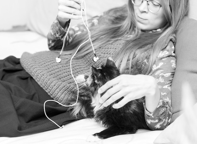 Young girl is lying on couch and playing with her pet cat with headphone wires. black and white photo. soft focus.