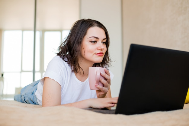 Young girl is lying at home on a bed with coffee and a laptop