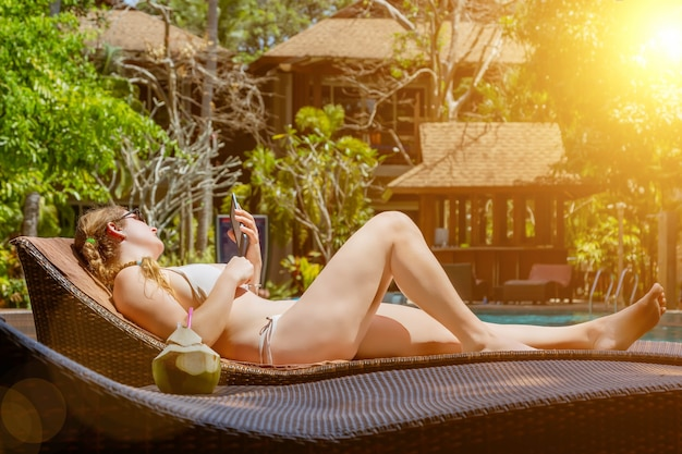 A young girl is lying on a lounger by the pool and reading an ebook nearby is fresh coconut juice