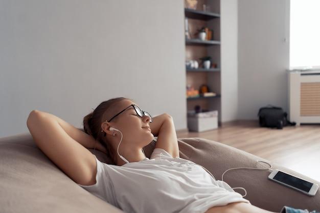 若い女の子は椅子のバッグに横たわって、自宅であなたの携帯電話から音楽を聴いています
