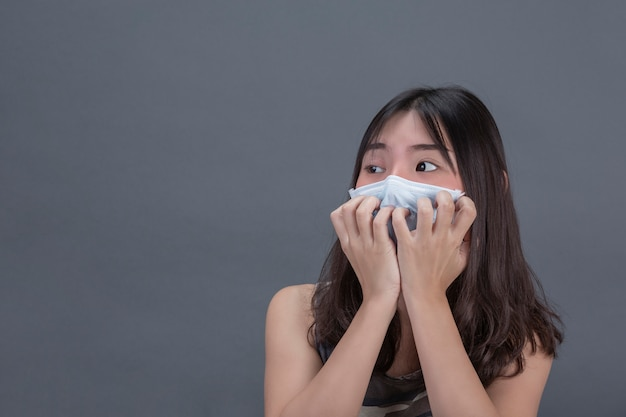 Young girl is mearing mask while covering by hand on gray wall.