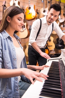 Young girl is playing piano in a music store.