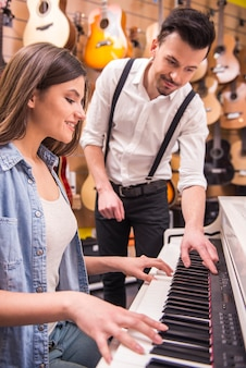 Young girl is playing the piano with man in the music store.