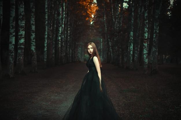 若い女の子は暗い森の中で黒いドレスを着てポーズをとっています