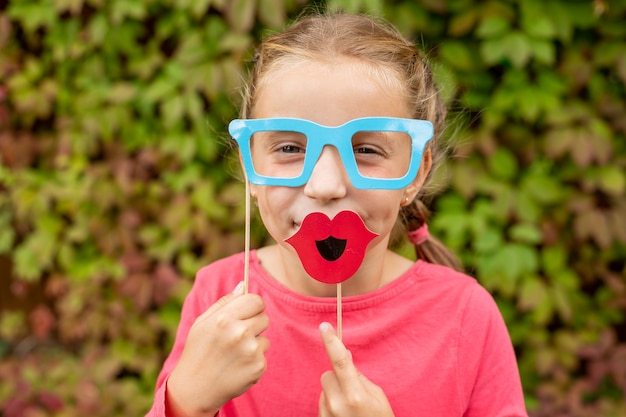 Young girl is preparing for birthday party with photo booth props.