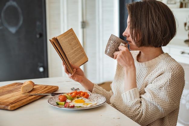 Молодая девушка читает старую книгу за завтраком. крупным планом руки и сервировка обеденного стола. стиль кантри. яичница со свежими овощами и чтение интересной книги по утрам