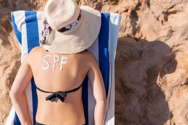 어린 소녀는 해변의 일광욕 의자에서 휴식을 취하고 있으며 그녀의 등에 썬 크림으로 만든 spf 단어가 있습니다. 태양 보호 계수 개념.