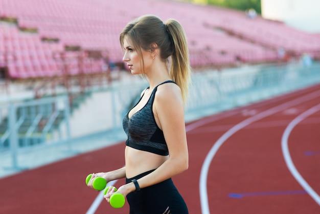 若い女の子はスタジアムで手にダンベルで実行されています。スポーツと健康の概念。