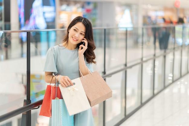 若い女の子はショッピングモールで電話を使って買い物をしています