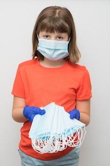 어린 소녀는 코로나 바이러스에 대한 수술 용 마스크 스택을 보여줍니다.