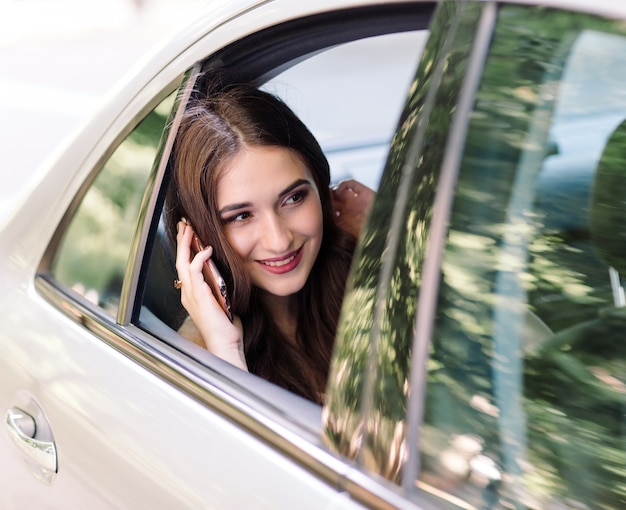 A young girl is sitting in the back seat of a car and is talking on the phone.