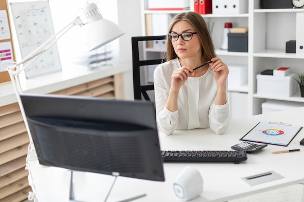 A young girl is sitting at the desk in the office, holding a pencil in her hand and looking at the monitor.