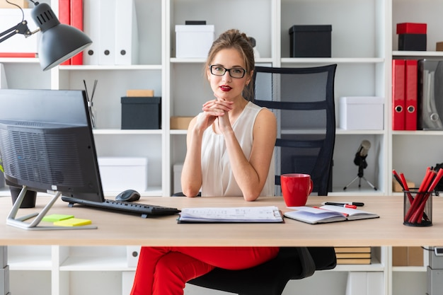 A young girl is sitting at the desk in the office