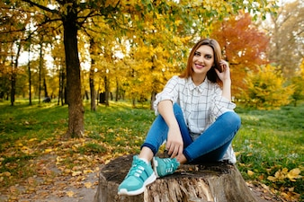 Young girl is sitting on a stump in the autumn park.