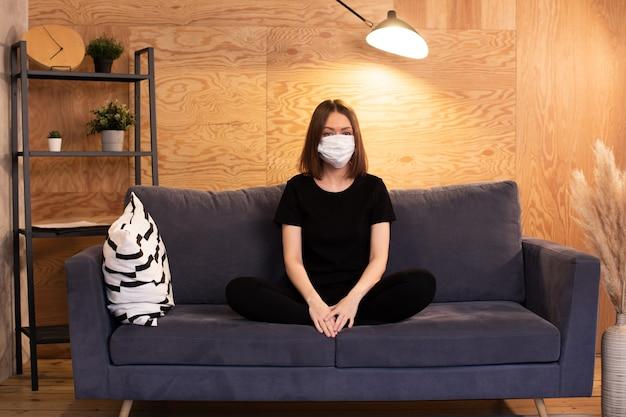 若い女の子は、マスクのソファに座って、カメラを見ています