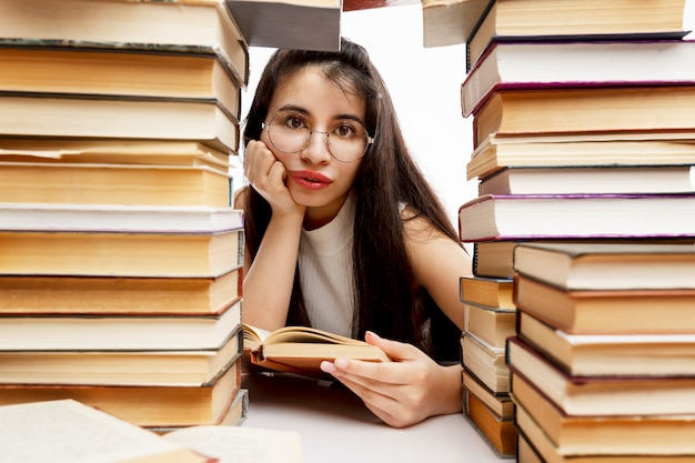 Young girl is sitting at a table with a pile of books. sad brunette with glasses. training and education. close-up.