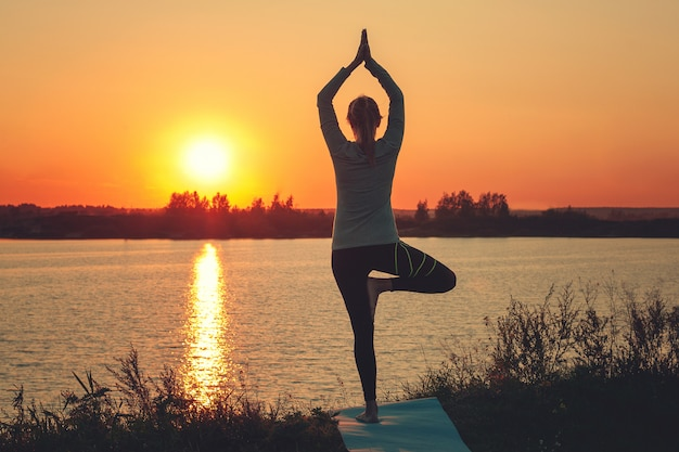 A young girl is standing on the lake at sunset, doing yoga.