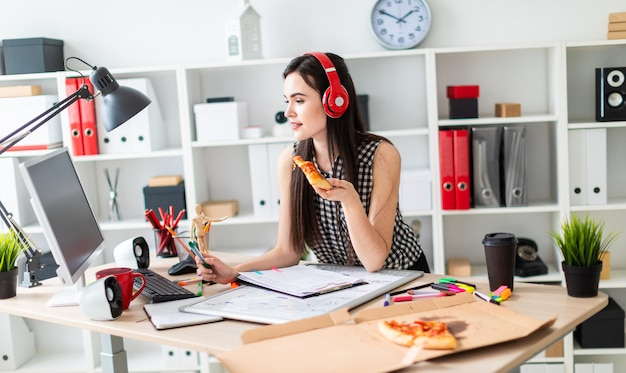 A young girl is standing near a table, holding a green marker and a piece of pizza in her hand before the girl on the table is a magnetic board on the head of the girl wearing headphones